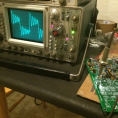 Photo of an oscilloscope testing a Mk II synth circuit board
