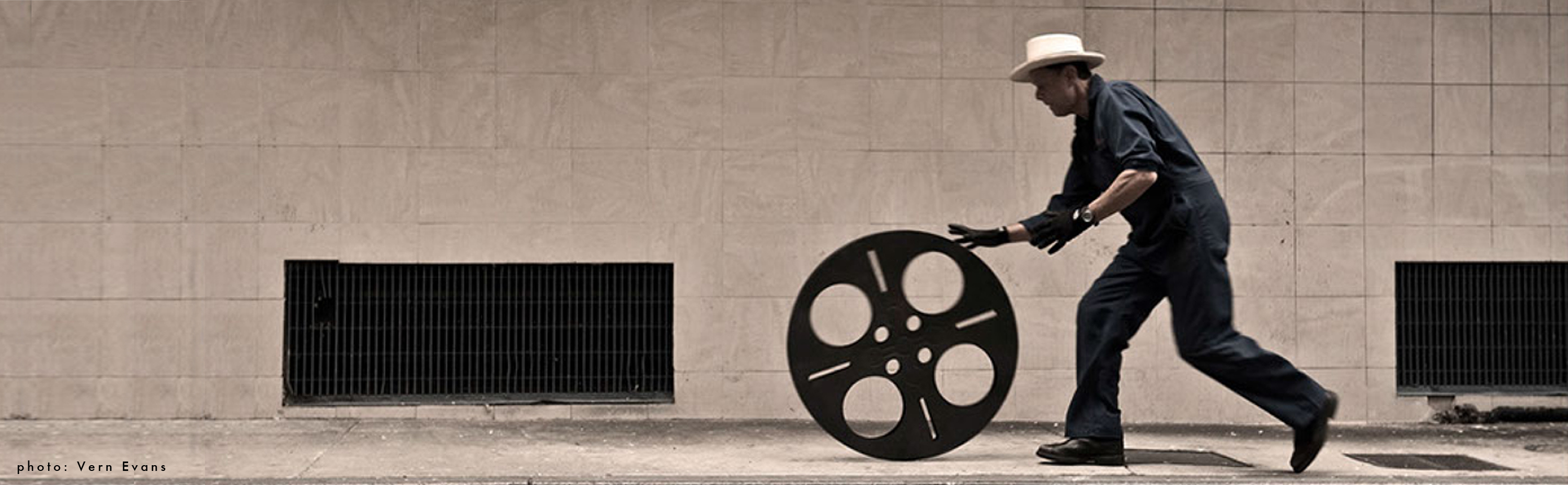 Photo of Carlos Grasso of Dumfuxx rolling a big film reel.
