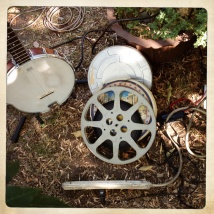 Photo of a banjo, film reels and a power strip on the ground at a Dumfuxx photo shoot.