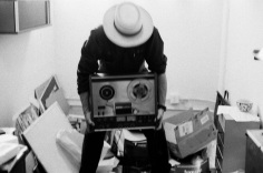 Photo of Carlos Grasso of Dumfuxx hoisting a reel-to-reel tape deck.