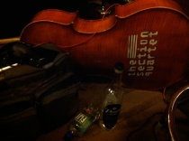 Photo of a cello, liquorand water bottles at Little Box Studios.