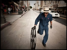 Photo of Carlos Grasso of Dumfuxx rolling a film reel on a street.