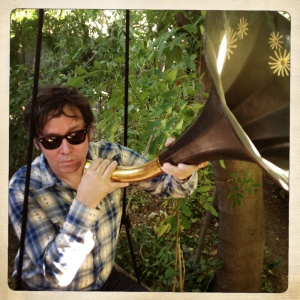 Photo of Grant-Lee Phillips blowing on a a Victrola horn.