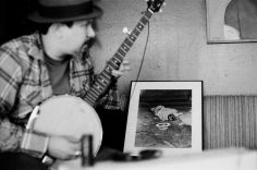 James Slay of Dumfuxx plays banjo at a Dumfuxx rehearsal with a Weegee photograph in the background.