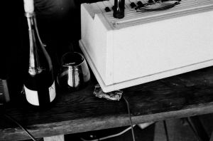 B&W photo of a bottle of wine and a plastic organ at a Dumfuxx rehearsal