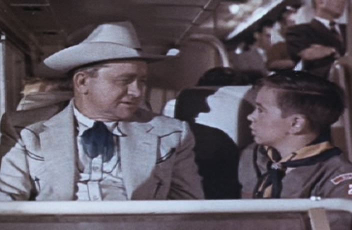 still of a man and boy scout on a bus